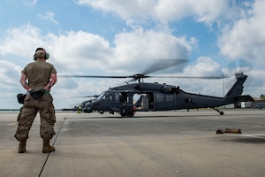Photo of an Airman observing an HH-60G Pave Hawk before takeoff.