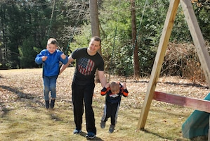 Staff Sgt. Andrew Menard, station commander, Southbridge, MA, pushes his sons on the backyard swing after a long day of recruiting virtually.