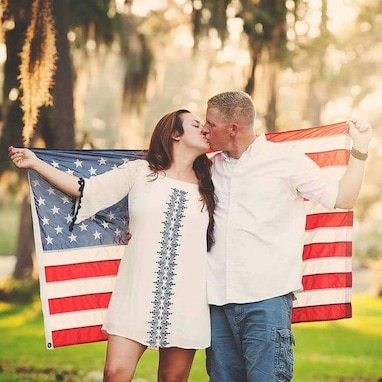 Army Soldier and wife kiss while holding U.S. flag