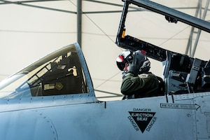 Photo of pilot putting his helmet on.