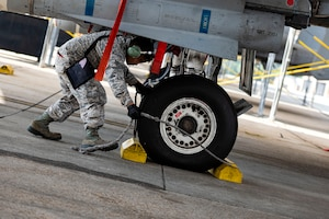 Photo of Airman removing chocks.