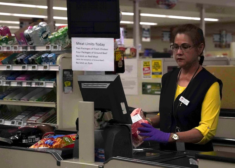 Amelia Camacho, a Defense Commissary Agency cashier, scans items at the commissary on Nellis Air Force Base, Nevada, March 24, 2020. Commissary workers continue to serve customers amid the COVID-19 pandemic while using personal protective equipment, such as gloves and face masks. (U.S. Air Force photo by Senior Airman Stephanie Gelardo)