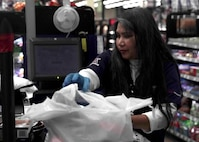 Josephine Rice, a cashier, packs a customer's items at the Exchange on Nellis Air Force Base, Nevada, March 24, 2020. The Exchange staff cleans and sanitizes work areas more frequently to protect customers and employees during the COVID-19 pandemic. (U.S. Air Force photo by Senior Airman Stephanie Gelardo)
