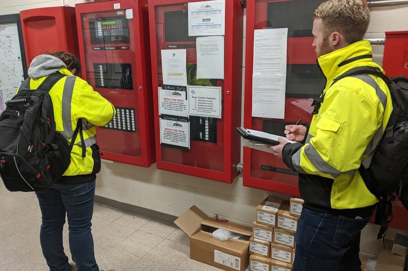 A woman and a man, both wearing yellow coats and black backpacks, make notes on clipboards.