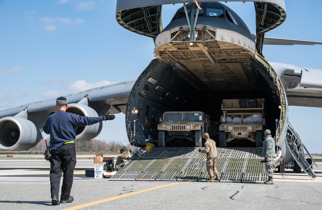 Dane Coward, left, 436th Aerial Port Squadron ramp supervisor, marshals a humvee down the forward loading ramp of a C-5M Super Galaxy March 26, 2020, at Dover Air Force Base, Delaware. Coward and his crew unloaded numerous Humvees off the Super Galaxy as required airlift operations continued during the evolving COVID-19 pandemic (U.S. Air Force photo by Roland Balik)