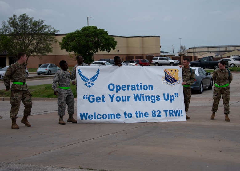 Airmen in Training leaders hold up a banner at Sheppard Air Force Base, Texas, March 27, 2020. The Airmen in Training are welcoming their new wingmen who are arriving via air lift to Sheppard. Usually the newest Airmen will arrive by bus, but to mitigate exposure Air Education and Training command opted to transport them via air lift. (U.S. Air Force photo by Senior Airman Pedro Tenorio)