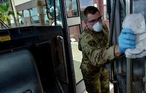 U.S. Air Force Staff Sgt. Colton Webber, 735th Air Mobility Squadron passenger terminal shift supervisor,   decontaminates the handrail after transporting passengers to and from the aircraft at Joint Base Pearl Harbor-Hickam, Hawaii, March 25, 2020.  U.S. Indo-Pacific Command (INDOPACOM) directed implementation of Health Protection Condition (HPCON) Charlie March 24, 2020.   (U.S. Air Force photo by Tech. Sgt. Anthony Nelson Jr. )