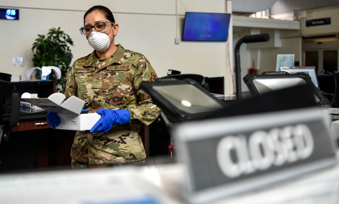 U.S. Air Force Airman 1st Class Griselda Hernandez, 735th Air Mobility Squadron passenger service agent,sanitizes the no-touch thermometers at the Air Mobility Command Passenger Terminal at Joint Base Pearl Harbor-Hickam, Hawaii, March 25, 2020.  Passenger terminal Airmen are screening passengers for fevers to help mitigate the spread of COVID-19.   (U.S. Air Force photo by Tech. Sgt. Anthony Nelson Jr.)