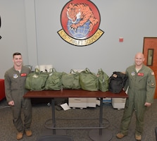 U.S. Air Force 1st Lt. Keegan Reynolds and Maj. Paul Voorhees, 535th Airlift Squadron C-17 pilots, with the 535th Airlift Squadron show what 6 feet of social distancing looks like using several flyers helmet bags at Joint Base Pearl Harbor-Hickam, Hawaii, March 25, 2020. U.S. Indo-Pacific Command (INDOPACOM) directed implementation of Health Protection Condition (HPCON) Charlie March 24, 2020. Charlie indicates substantial risk and sustained community transmission of the COVID-19 disease.   (U.S. Air Force photo by Tech. Sgt. Anthony Nelson Jr.)