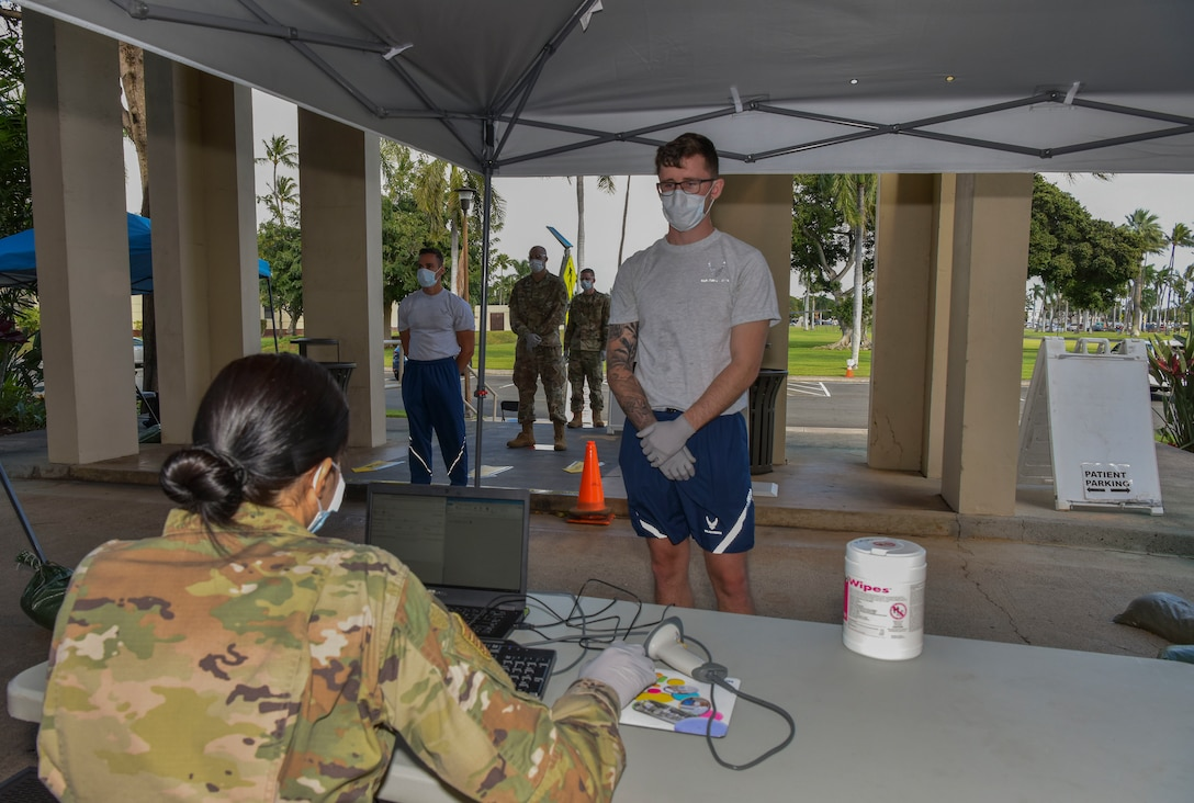 U.S. Air Force Airmen assigned to the 15th Medical Group demonstrate proper social distancing outside the 15th Medical Group Clinic at the pharmacy processing area at Joint Base Pearl Harbor-Hickam, Hawaii, March 25, 2020. U.S. Indo-Pacific Command directed implementation of Health Protection Condition Charlie March 24, 2020. Charlie indicates substantial risk and sustained community transmission of the COVID-19 disease.
