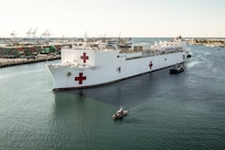 A hospital ship arrives at a port.