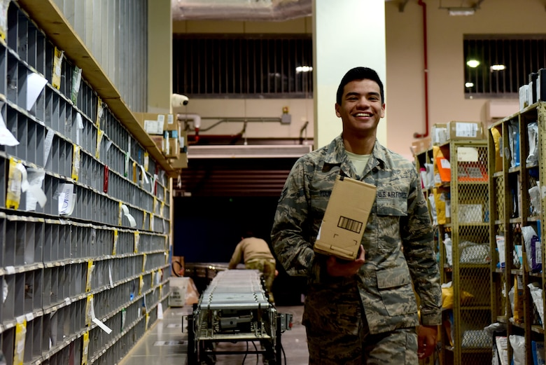 U.S. Air Force Airman 1st Class Daniel Young, 31st Force Support Squadron postal clerk, transfers a package from sorting to the shelf at the Aviano Post Office, Aviano Air Base, Italy, March 25, 2020. Due to the recent surge of arrivals, the post office has had full shelves and an abundance of packages awaiting pickup. (U.S. Air Force photo by Staff Sgt. Kelsey Tucker)