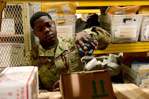 U.S. Air Force Airman 1st Class DeAnthony Lewis, 31st Force Support Squadron postal clerk, scans the label of a package at the Aviano Post Office, Aviano Air Base, Italy, March 25, 2020. Boxes entering the post office are scanned several times, entering them into the system and sending an email to the recipient notifying them of the package's arrival. (U.S. Air Force photo by Staff Sgt. Kelsey Tucker)