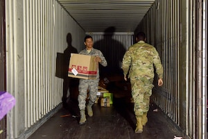 U.S. Air Force Airman 1st Class Daniel Young, left, and Airman 1st Class DeAnthony Lewis, 31st Force Support Squadron postal clerks, unload mail from a delivery truck at Aviano Air Base, Italy, March 25, 2020. Due to restrictions placed on the local economy in order to slow the spread of COVID-19, post office Airmen have found their services in much higher demand. (U.S. Air Force photo by Staff Sgt. Kelsey Tucker)
