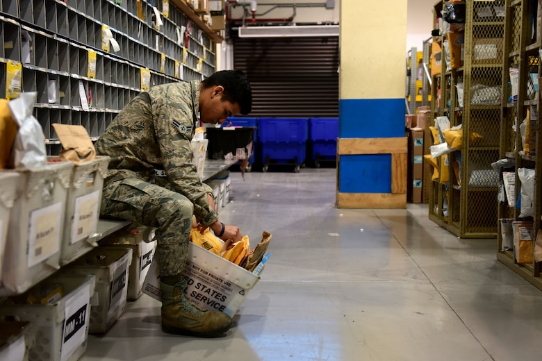 U.S. Air Force Airman 1st Class Daniel Young, 31st Force Support Squadron postal clerk, places labels onto packages at the Aviano Post Office, Aviano Air Base, Italy, March 25, 2020. After sorting, each package receives a label denoting the recipient and its location on the shelf. (U.S. Air Force photo by Staff Sgt. Kelsey Tucker)