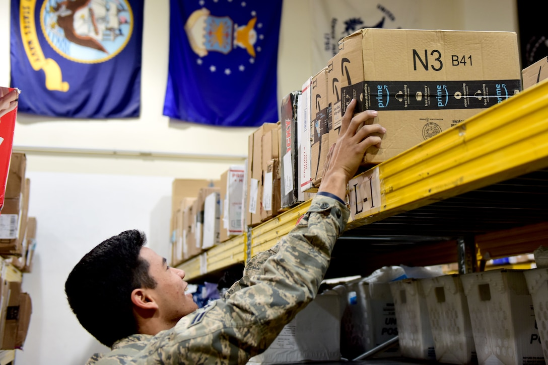 U.S. Air Force Airman 1st Class Daniel Young, 31st Force Support Squadron postal clerk, places packages onto a shelf at the Aviano Post Office, Aviano Air Base, Italy, March 25, 2020. The post office receives packages for service members, dependents, and civilians assigned to the base. (U.S. Air Force photo by Staff Sgt. Kelsey Tucker)