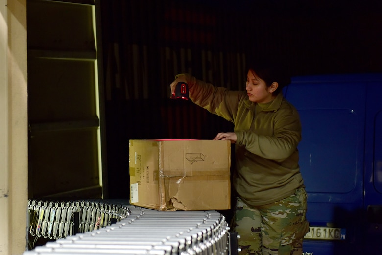 U.S. Air Force Staff Sgt. Eddith Guaman, 31st Force Support Squadron postal supervisor, scans an incoming package at the Aviano Post Office, Aviano Air Base, Italy, March 25, 2020. After unloading packages from the trucks, post office Airmen scan them into their system, sort them, and then either deliver them to members' mailboxes or inform them via email that they have a package ready for pickup. (U.S. Air Force photo by Staff Sgt. Kelsey Tucker)