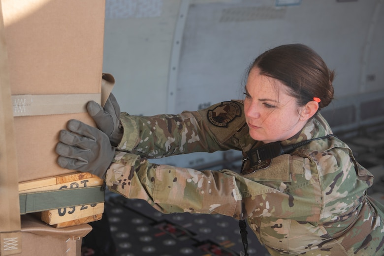 Tech. Sgt. Melissa Durkin-Willman, 727th Air Mobility Squadron noncommissioned officer in charge of passenger travels, pushes a cargo crate inside of a commercial aircraft March 24, 2020, at RAF Mildenhall, England. Air transportation Airmen must often rearrange cargo, as not all assets on board an aircraft are destined for the same location. (U.S. Air Force photo by Airman 1st Class Joseph Barron)