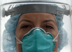 A portrait of an Air Force nurse wearing facial protective gear.