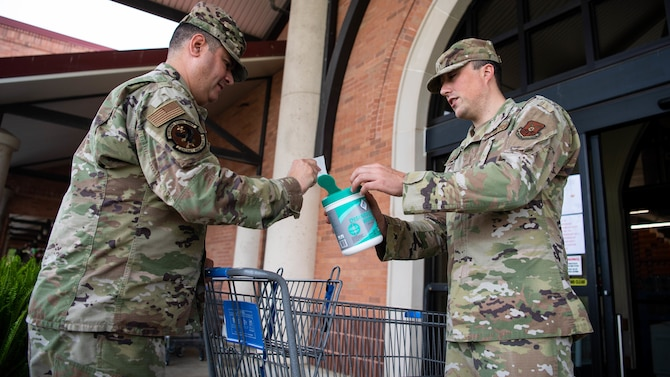 Tech. Sgt. Tom Parsons, 2nd Mission Support Group executive assistant, hands out sanitizing wipes at the commissary at Barksdale Air Force Base, La., March 24, 2020. The Barksdale commissary has implemented a number of safety guidelines to stop the spread of germs, including: sanitizing registers and door handles more frequently than normal, marking lines on the floor to ensure people keep a six foot distance and even making routine intercom announcements to remind customers of common health guidelines. (U.S. Air Force photo by Airman 1st Class Jacob B. Wrightsman)