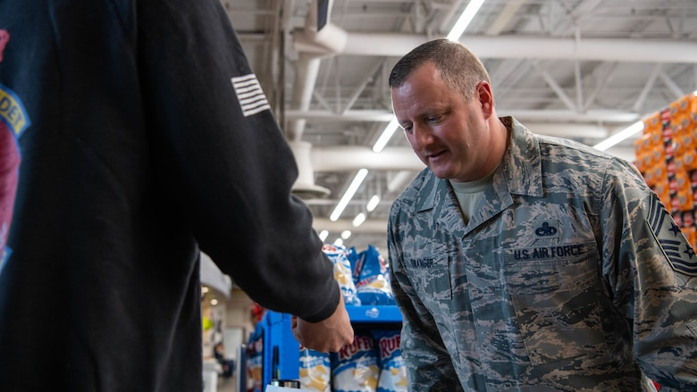 Chief Master Sgt. Joshua Swanger, 2nd Bomb Wing command chief, checks an identification card at the commissary at Barksdale Air Force Base, La., March 21, 2020. To mitigate the influx of shoppers and to keep Airmen and their families safe, Barksdale's commissary began checking identification cards at the front doors, to ensure only authorized personnel were accessing the store. (U.S. Air Force photo by Airman 1st Class Jacob B. Wrightsman)