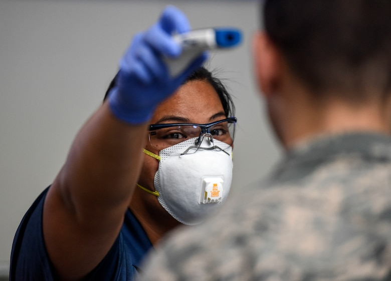 Kuhina Talimalie, 735th Air Mobility Squadron passenger service and baggage agent, tests a no-touch thermometer on an U.S. Air Force Airman at the Air Mobility Command Passenger Terminal at Joint Base Pearl Harbor-Hickam, Hawaii, March 25, 2020.