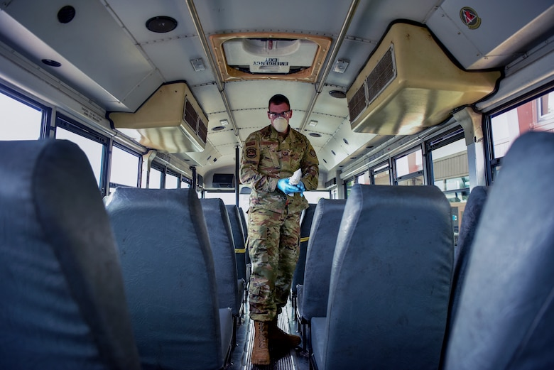 U.S. Air Force Staff Sgt. Colton Webber,  735th Air Mobility Squadron passenger terminal shift supervisor, decontaminates a bus after transporting passengers to and from the aircraft at Joint Base Pearl Harbor-Hickam, Hawaii, March 25, 2020.