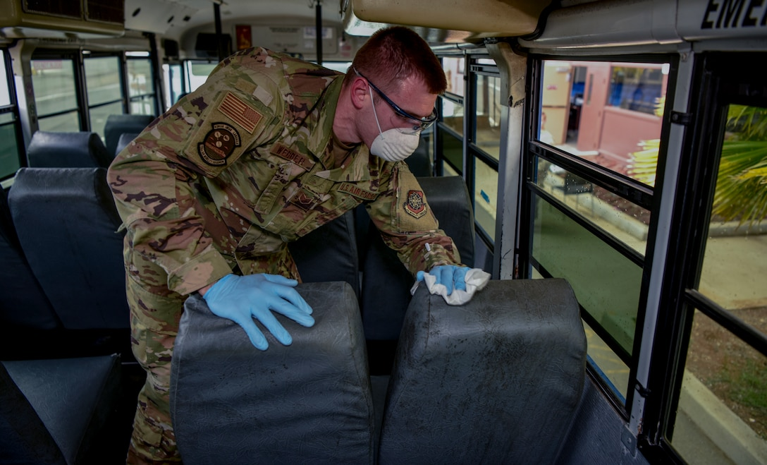 U.S. Air Force Staff Sgt. Colton Webber,  735th Air Mobility Squadron passenger terminal shift supervisor,  decontaminates a bus after transporting passengers to and from the aircraft at Joint Base Pearl Harbor-Hickam, Hawaii, March 25, 2020.  U.S. Indo-Pacific Command (INDOPACOM) directed implementation of Health Protection Condition (HPCON) Charlie March 24, 2020.  (U.S. Air Force photo by Tech. Sgt. Anthony Nelson Jr. )