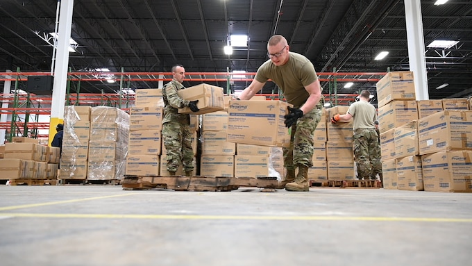 (From left) U.S. Air Force Tech. Sgt. Bradly Tuthill and U.S. Air Force Master Sgt. Richard Malloy, both ground transportation specialists with the 175the Logistics Readiness Squadron, prepare and load boxes of medical supplies and equipment March 19, 2020, at the Maryland Strategic National Stockpile location. All assets provided were prioritized for health care workers and hospitals in response to the COVID-19 pandemic. (U.S. Air National Guard photo by Master Sgt. Christopher Schepers)