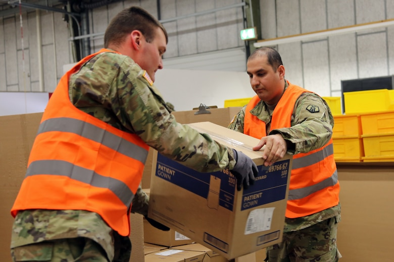 U.S. Army Reserve Sgt. Farid Tehrani, right, a supply sergeant with Medical Support Unit-Europe, 7th Mission Support Command, and U.S. Army Sgt. Roger Rood, a biomedical equipment specialist with the 8th Medical Logistics Company, 421st Multifunctional Medical Battalion, 30th Medical Brigade, 21st Theater Sustainment Command, load boxes of medical supplies onto a pallet at the U.S. Army Medical Materiel Center, Europe warehouse in Pirmasens, Germany, March 26, 2020. 7th MSC and 21st TSC Soldiers are supporting the shipping and receiving functions in the warehouse to help with the high demand of Army Class VIII medical supplies during the COVID-19 pandemic.