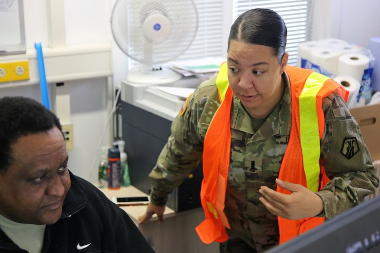 U.S. Army Reserve 1st Lt. Ava Carter, a clinical social worker with Medical Support Unit-Europe, 7th Mission Support Command, discusses warehouse functions with Wilbert Stephens, Chief of Transportation at U.S. Army Medical Materiel Center, Europe in Pirmasens, Germany, March 26, 2020. 7th MSC Soldiers are supporting the shipping and receiving functions in the warehouse to help with the high demand of Army Class VIII medical supplies during the COVID-19 pandemic.