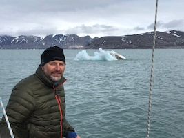 Mr. Stephen Skinner poses on the deck of his sailboat, while sailing to island of Svalbard, north of the Arctic Circle.