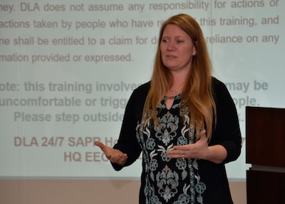 Robin Rogers in front of a slide screen giving training