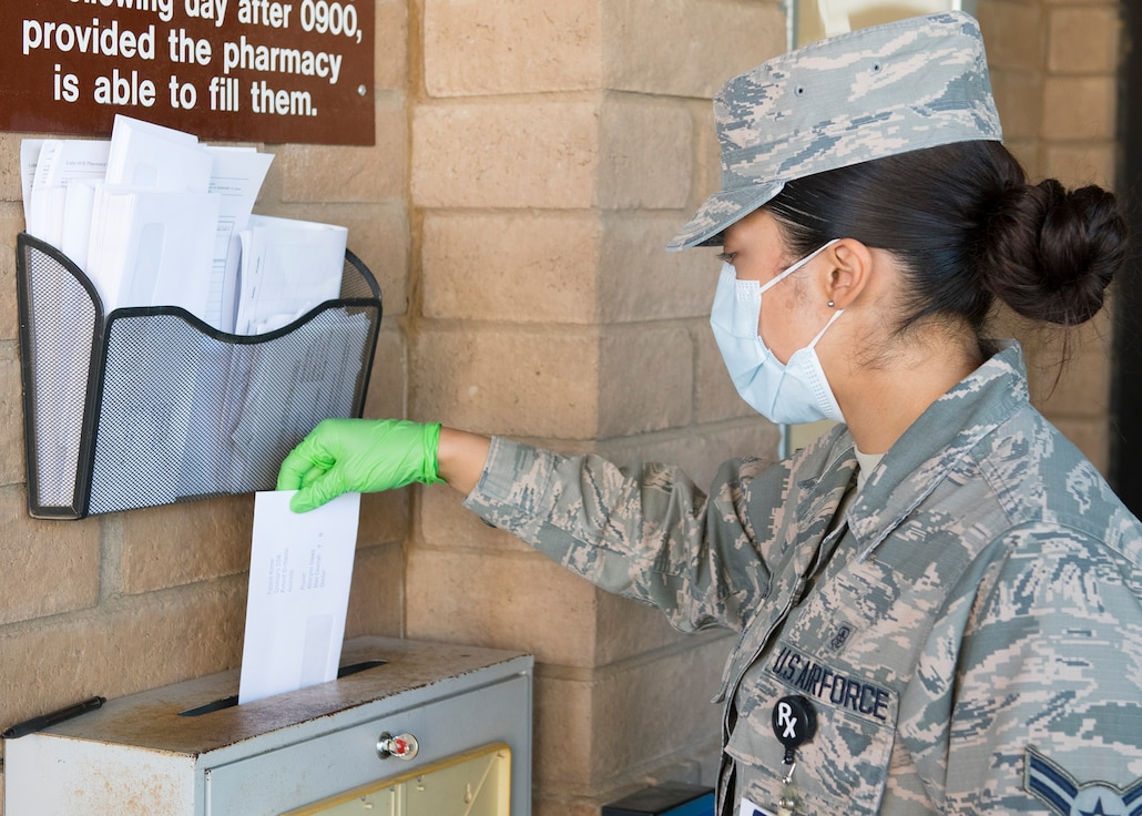 Airman 1st Class Erika Tolentino, 56th Medical Group pharmacy technician, places a prescription order in a drop off box March 26, 2020, at Luke Air Force Base, Ariz.
