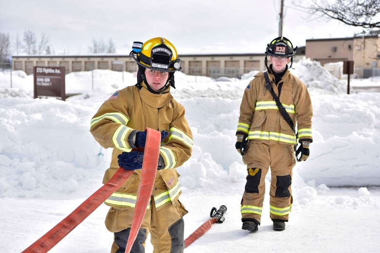 Airman Lily Lane, a 354th Civil Engineer Squadron firefighter, pulls a hose from a fire truck during a training exercise on Eielson Air Force Base, Alaska, March 26, 2020. Eielson firefighters train for multiple types of situations such as cold-weather response, forest fire containment, structure and vehicle fires, as well as medical emergencies. (U.S. Air Force photo by Senior Airman Beaux Hebert)