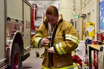 Airman Lily Lane, a 354th Civil Engineer Squadron firefighter, dons fire protection equipment during a training exercise on Eielson Air Force Base, Alaska, March 26, 2020. In 2019, the Eielson fire department responded to approximately 500 calls, the majority being structural and medical. (U.S. Air Force photo by Senior Airman Beaux Hebert)
