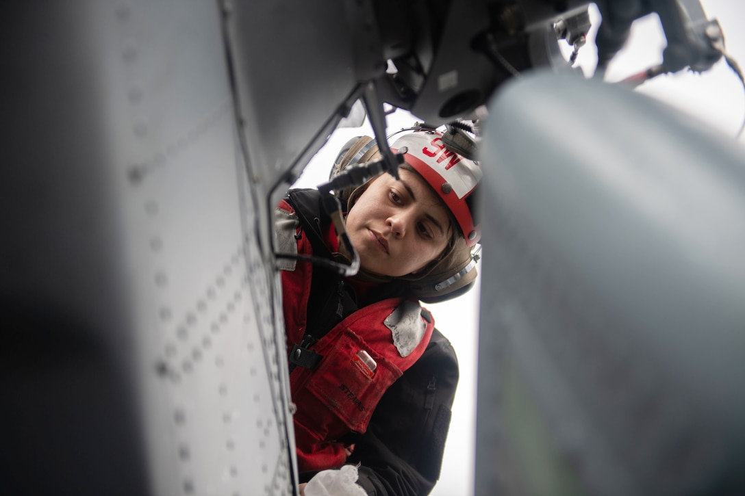A sailor looks down at part of a helicopter.