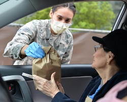 SrA Reanne Kohlus, a dental technician assigned to the 59th Dental Group, hands a prescription over to a beneficiary March 30, 2020, at Joint Base San Antonio- Lackland, Texas. The 59th Medical Wing is providing curbside service until further notice in front of the Wilford Hall Ambulatory Surgical Center in support of social distancing recommendations and to increase efforts to mitigate further spread of the novel coronavirus.
