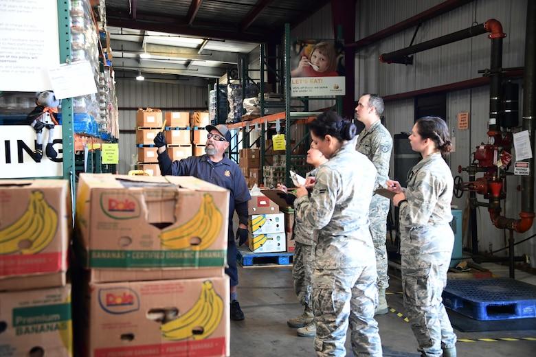 A photo of California Air National Guardsmen receiving instructions on inventorying food by a Foodbank Santa Barbara employee.