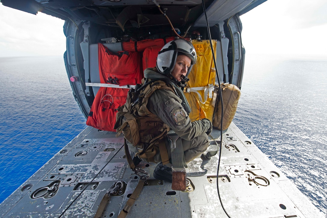 A sailor kneels inside of a helicopter with open doors on both sides and the ocean seen below.