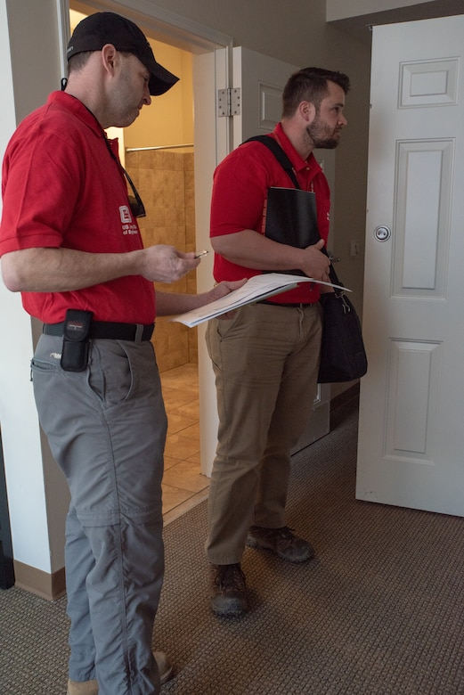 Two men wearing red polo shirts inspect a room.