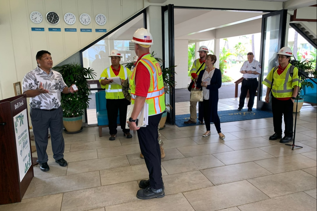 Engineers wearing yellow vests and white hard hats speak with a hotel manager wearing a Hawaiian shirt.