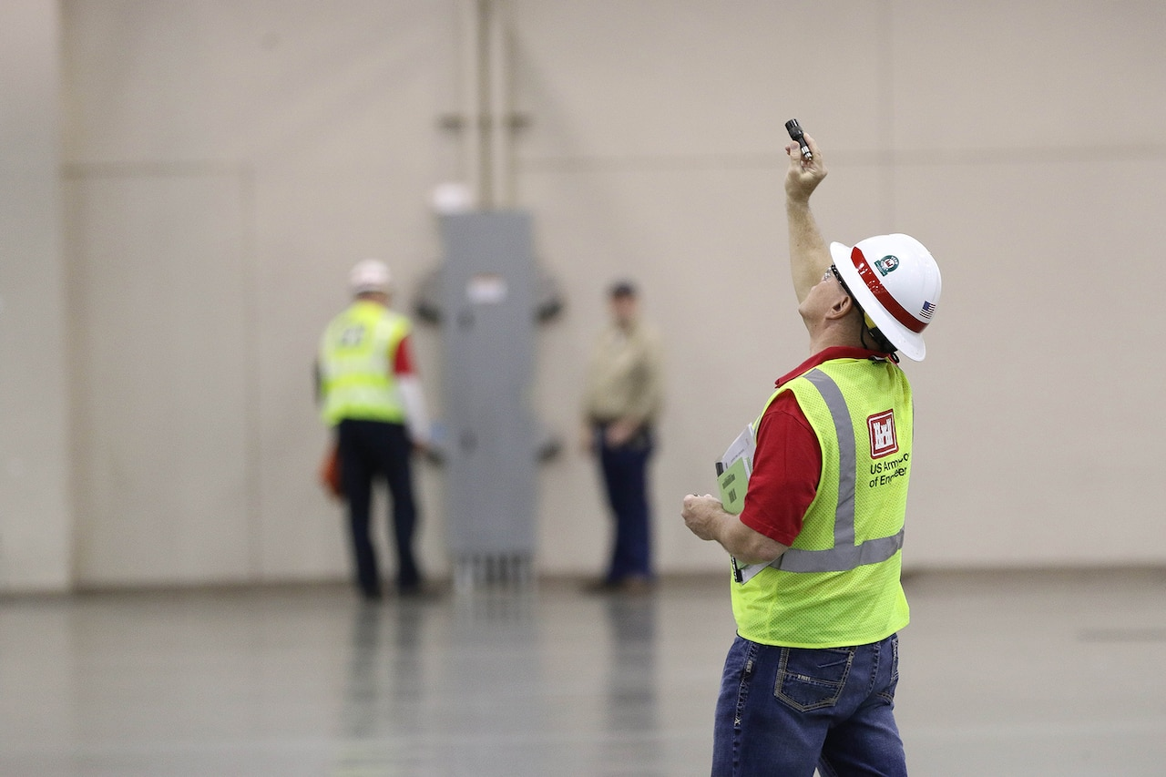 A man wearing a yellow vest and a white hard hat aims a device at a ceiling.