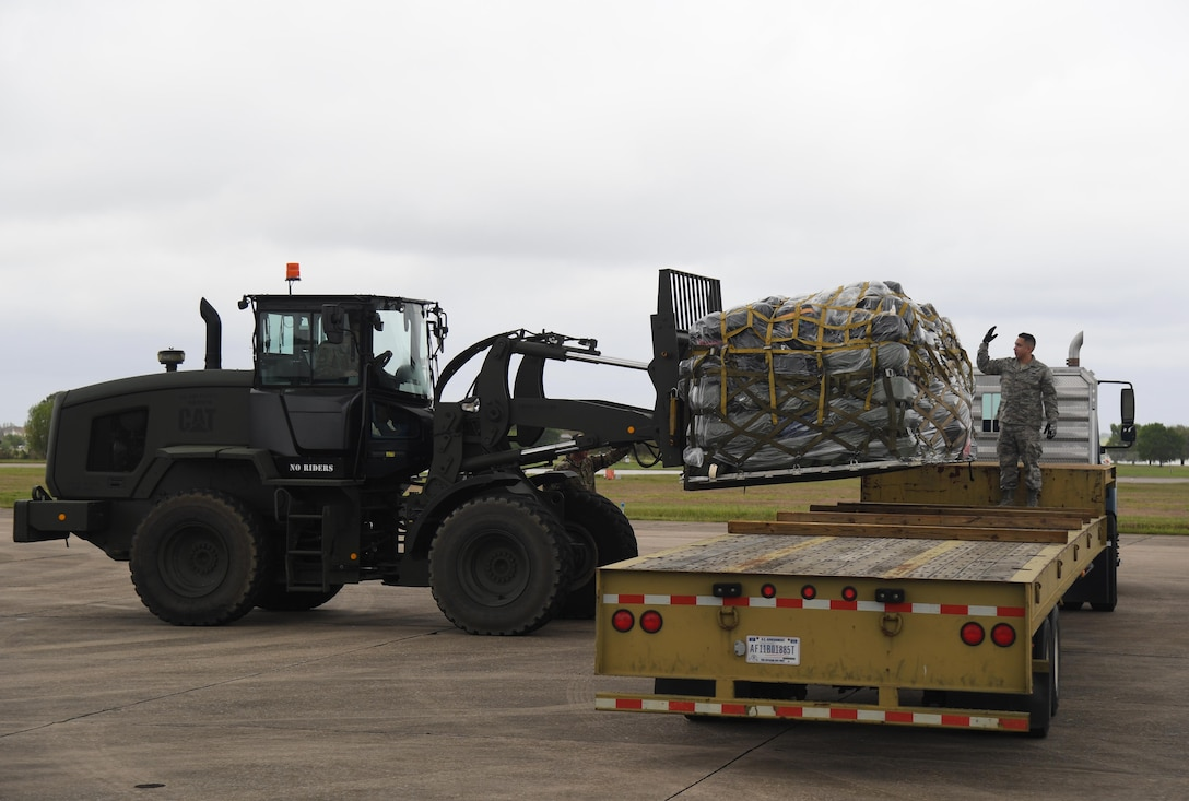 A pallet of duffel bags being loaded on a flat bed truck.