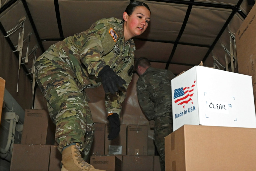A soldier loads a truck.
