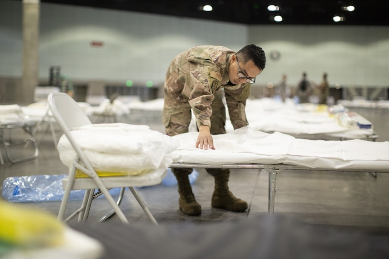 A photo of U.S. Air National Guard Mario Lopez-Casas putting sheets on a hospital bed inside the Los Angeles Convention Center.