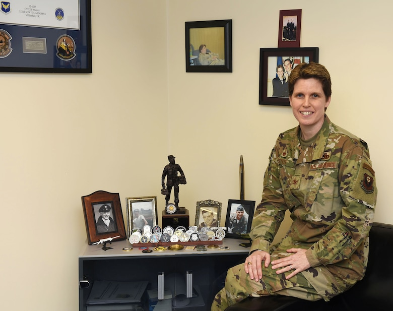 Colonel Michelle Estes, 352nd Special Operations Maintenance Group commander, poses for a photo with pictures of her family, several members of which have also served in the military, at RAF Mildenhall, England, March 18, 2020. As part of Women's History Month, Estes shared her experiences and life lessons from her 23-year career in the Air Force. (U.S. Air Force photo by Karen Abeyasekere)