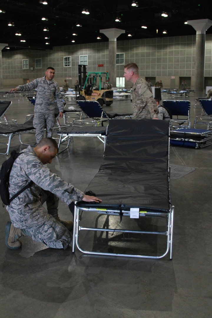 A photo of three U.S. Air National Guard members making a assembling medical beds inside the Los Angeles Convention Center.