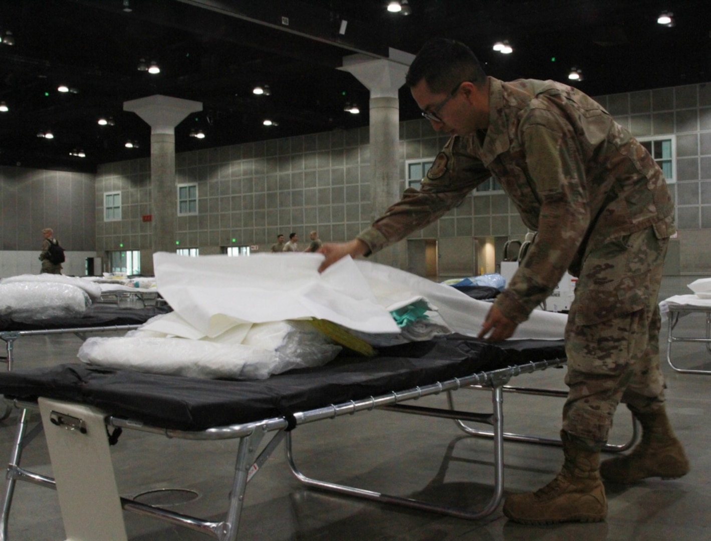 A photo of U.S. Air National Guard Tech. Sgt. Mario Lopez-Casas making a temporary hospital bed inside the Los Angeles Convention Center.