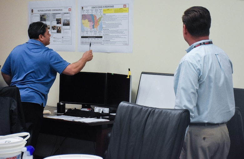 Antonio Santoscruz, (left) U.S. Army Engineering and Support Center, Huntsville Emergency Operations Center operations and plans specialist, refers to a chart of COVID-19 response effort information during an EOC meeting with James Buhr, EOC team member (right) March 25.